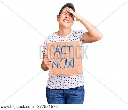 Young woman with short hair holding act now banner stressed and frustrated with hand on head, surprised and angry face
