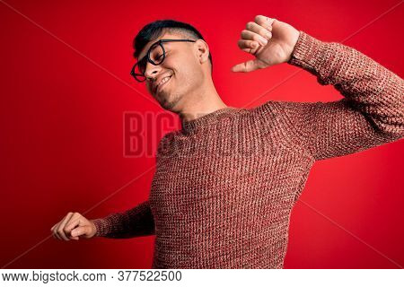 Young handsome hispanic man wearing nerd glasses over red background stretching back, tired and relaxed, sleepy and yawning for early morning