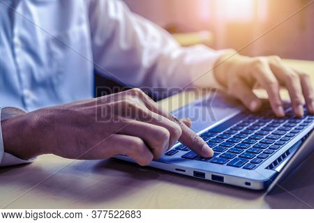 Businessman Hand Typing On Computer Keyboard Of A Laptop Computer In Office. Business And Finance Co