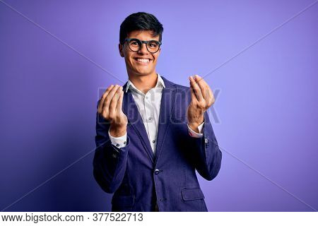 Young handsome business man wearing jacket and glasses over isolated purple background doing money gesture with hands, asking for salary payment, millionaire business
