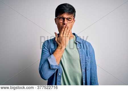 Young handsome man wearing casual shirt and glasses over isolated white background bored yawning tired covering mouth with hand. Restless and sleepiness.