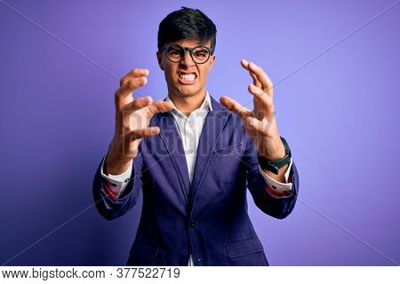 Young handsome business man wearing jacket and glasses over isolated purple background Shouting frustrated with rage, hands trying to strangle, yelling mad