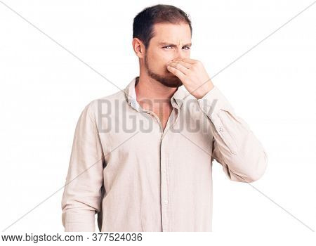 Young handsome caucasian man wearing casual clothes smelling something stinky and disgusting, intolerable smell, holding breath with fingers on nose. bad smell