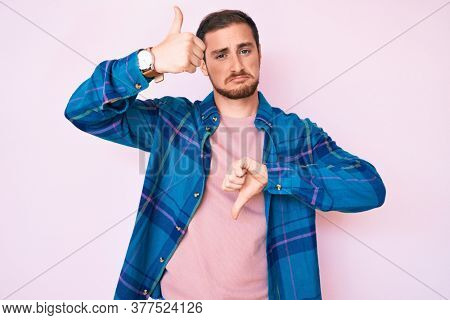 Young handsome man wearing casual clothes doing thumbs up and down, disagreement and agreement expression. crazy conflict