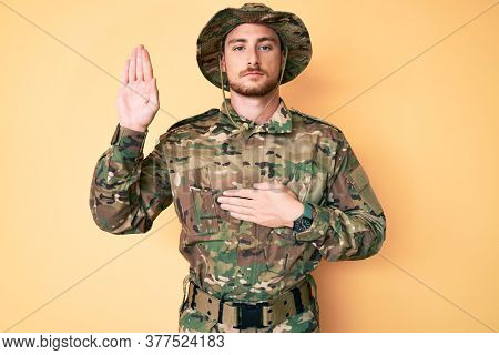 Young caucasian man wearing camouflage army uniform swearing with hand on chest and open palm, making a loyalty promise oath