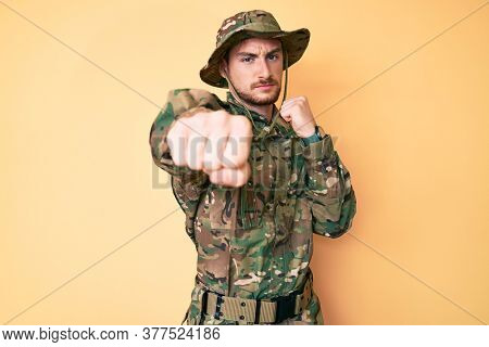 Young caucasian man wearing camouflage army uniform punching fist to fight, aggressive and angry attack, threat and violence