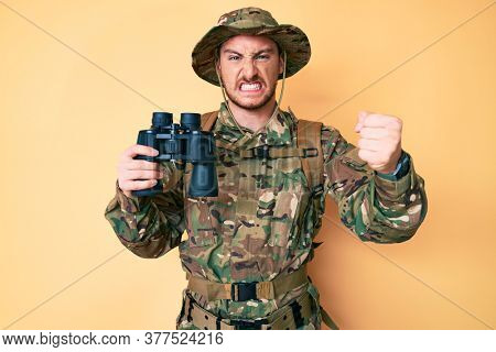 Young caucasian man wearing camouflage army uniform holding binoculars annoyed and frustrated shouting with anger, yelling crazy with anger and hand raised