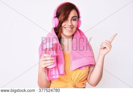 Young beautiful woman wearing towel and headphones holding bottle of water smiling happy pointing with hand and finger to the side