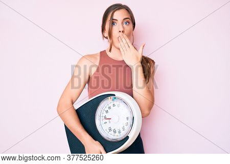 Beautiful young caucasian woman holding weight machine to balance weight loss covering mouth with hand, shocked and afraid for mistake. surprised expression