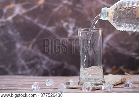 Pouring Drinking Water In Glasses On Wood Table Background And Space For Text