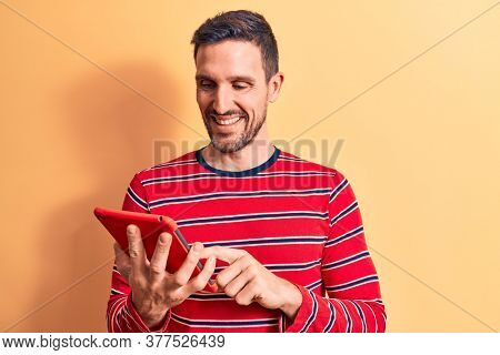 Young handsome man holding touchpad standing over isolated yellow background looking positive and happy standing and smiling with a confident smile showing teeth