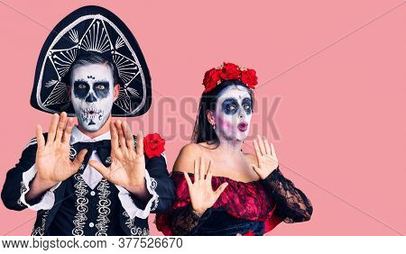 Young couple wearing mexican day of the dead costume over background moving away hands palms showing refusal and denial with afraid and disgusting expression. stop and forbidden.
