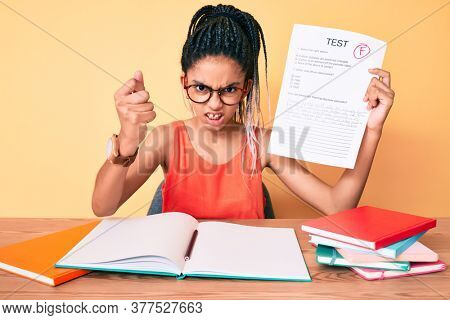 Young african american girl child with braids showing failed exam annoyed and frustrated shouting with anger, yelling crazy with anger and hand raised