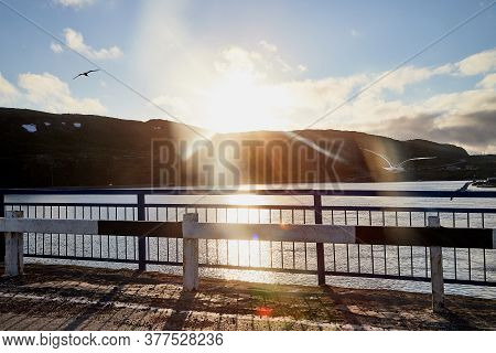 View On Railing Of Bridge And Water Of River Below. Sun From Hills In Nature Landscape In The Evenin