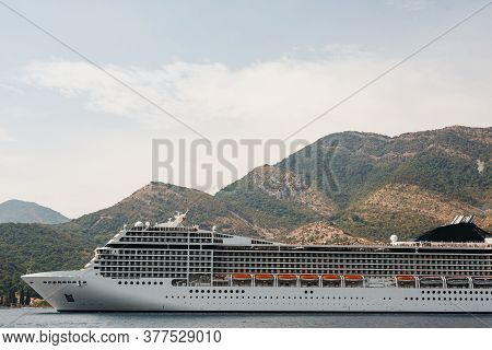 A Close-up Of A Large Cruise Liner In The Kotor Bay Of Montenegro, Against The Backdrop Of A Mountai