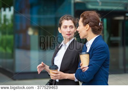 Female Business Colleagues With Takeaway Coffee Cups Walking Together Outdoors, Talking, Discussing