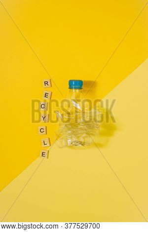 Vertical Color Image With An Overhead View Of A Transparent And Crushed Plastic Bottle With Blue Cap