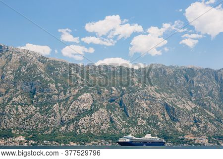A Huge Multi-deck Cruise Liner In Kotor Bay, Against The Backdrop Of A Mountain Above The City Of Do
