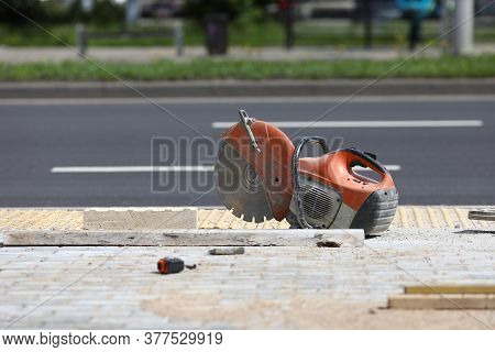 Roadwork Gas Saw Is On Sidewalk. Buying Gas Saw For Concrete Or Metal Concept