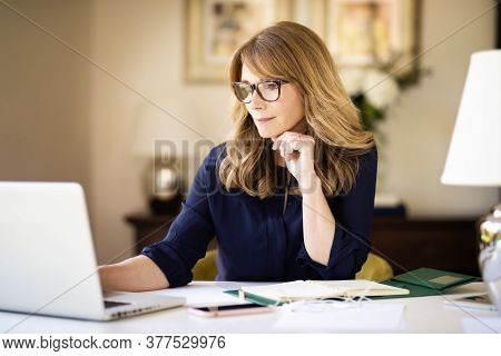 Shot Of Middle Aged Businesswoman Sitting At Desk And Using Laptop While Working From Home. Home Off