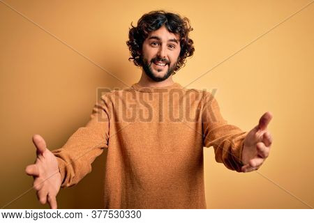 Young handsome man with beard wearing casual sweater standing over yellow background looking at the camera smiling with open arms for hug. Cheerful expression embracing happiness.