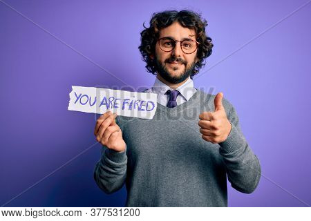 Handsome business man with beard holding you are fired message over purple background happy with big smile doing ok sign, thumb up with fingers, excellent sign