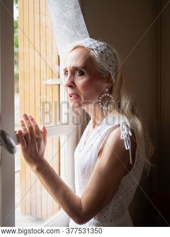 Vertical Portrait Of An Anxious Mature Woman Standing And Looking Through The Window