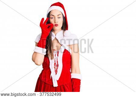 Young beautiful caucasian woman wearing santa claus costume mouth and lips shut as zip with fingers. secret and silent, taboo talking
