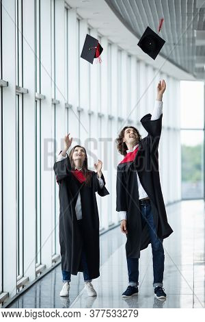 Man And Woman Graduates Throwing Graduation Hats In The Air. Happy Couple Of Students In The Graduat