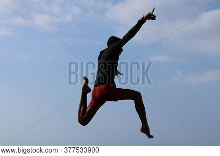 Happy man jumping above blue sky background. Young cheerful Indonesian jumps. A teenager in a good mood jumps in the air. Sunny tropical day