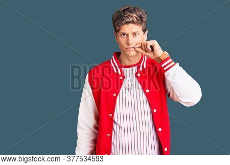 Young handsome man wearing baseball uniform mouth and lips shut as zip with fingers. secret and silent, taboo talking