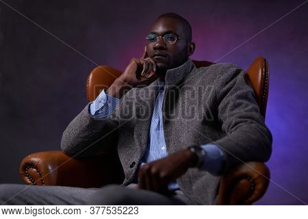 Confident Stylish African American Businessman Sitting On A Luxurious Leather Sofa, Looks Pensive. S