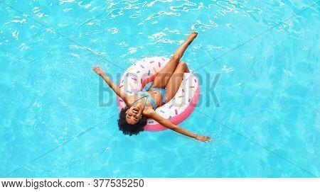Amazing Black Girl In Bikini Swimming On Inflatable Ring In Pool, Overhead View. Panorama