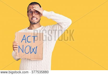 Young handsome man holding act now banner stressed and frustrated with hand on head, surprised and angry face