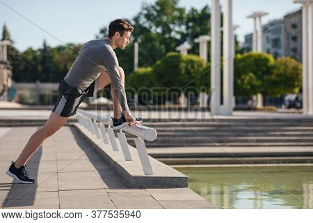 Morning Stretching. Athletic Guy In Sportswear Puts His Foot On Railing And Does Exercises In Park,