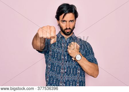 Young handsome hispanic bohemian man wearing hippie style over pink background Punching fist to fight, aggressive and angry attack, threat and violence