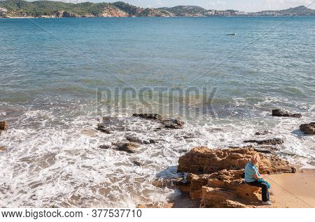 Portals Vells, Balearic Islands/spain; November 2014: Older Woman Sitting On A Rock On The -mediterr