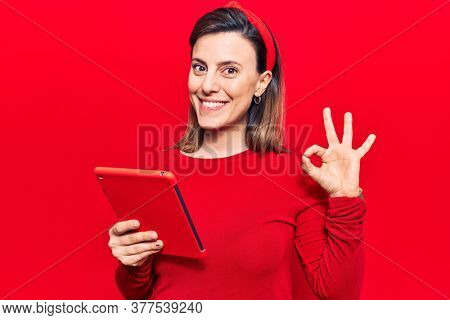 Young beautiful woman holding touchpad doing ok sign with fingers, smiling friendly gesturing excellent symbol