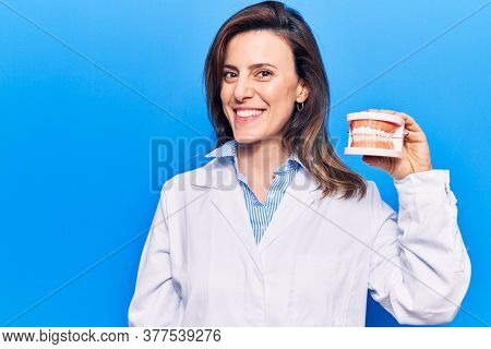 Young beautiful woman wearing dentist coat holding denture looking positive and happy standing and smiling with a confident smile showing teeth