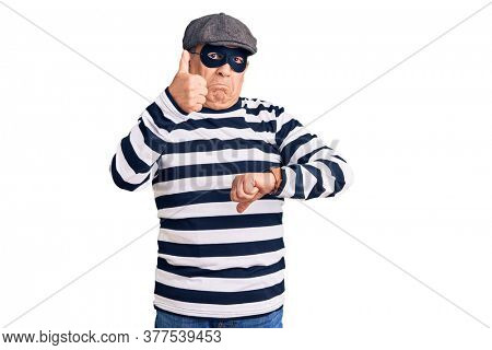 Senior handsome man wearing burglar mask and t-shirt doing thumbs up and down, disagreement and agreement expression. crazy conflict