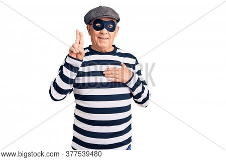 Senior handsome man wearing burglar mask and t-shirt smiling swearing with hand on chest and fingers up, making a loyalty promise oath