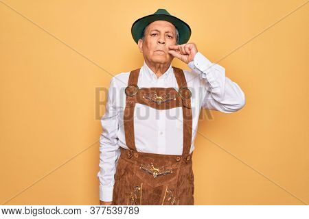 Senior grey-haired man wearing german traditional octoberfest suit over yellow background mouth and lips shut as zip with fingers. Secret and silent, taboo talking