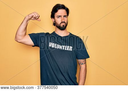 Young handsome hispanic volunteer man wearing volunteering t-shirt as social care Strong person showing arm muscle, confident and proud of power