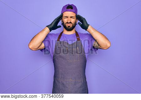 Young handsome hispanic man with bear wearing professional apron working as tattoo artist suffering from headache desperate and stressed because pain and migraine. Hands on head.