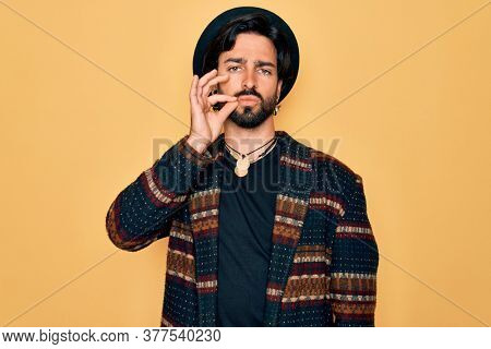 Young handsome hispanic bohemian man wearing hippie style and boho hat mouth and lips shut as zip with fingers. Secret and silent, taboo talking