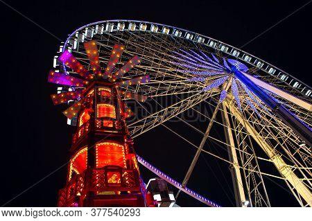 Ferris Wheel At Night . Amusement Park Illuminated In The Night