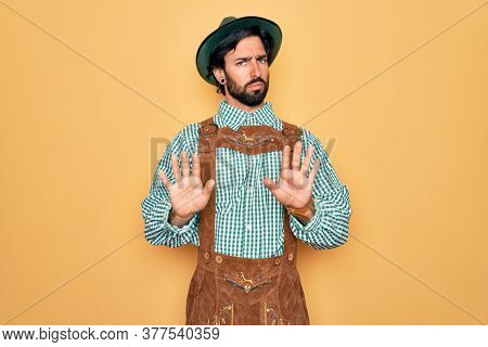 Young handsome man wearing tratidional german octoberfest custome for Germany festival Moving away hands palms showing refusal and denial with afraid and disgusting expression. Stop and forbidden.