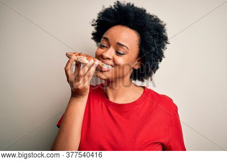Young beautiful african american afro woman smiling happy and confident. Standing with smile on face eating delicious slice of italian pizza over isolated white background
