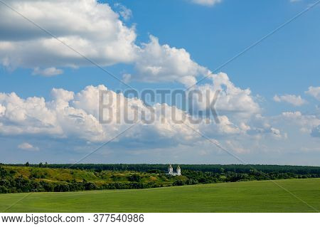 White Clouds Over Green Fields And Forests. Little White Church On The Horizon