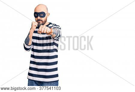 Young handsome man wearing burglar mask punching fist to fight, aggressive and angry attack, threat and violence